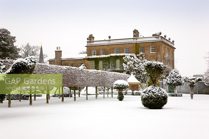 Oblique view of the west front with hedges and topiary at Highgrove, covered in snow, January 2010.