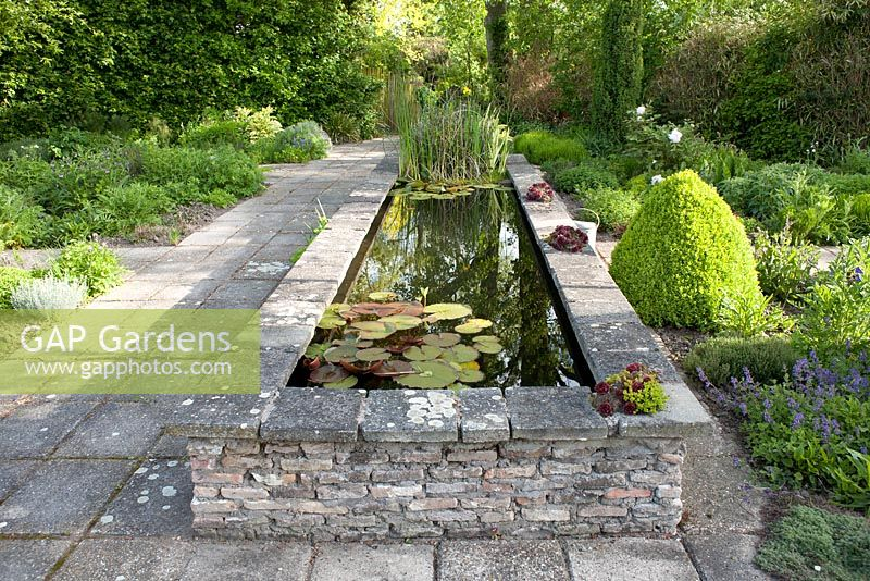 A Rectangular Raised Pond Surrounded By Beds Of Perennials.