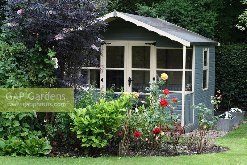 Painted Wooden Summerhouse In An Urban Garden With A Country Feel