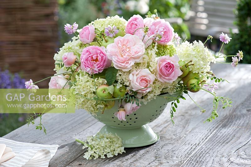 Pink flower arrangement in kitchen colander and ceramic bowl