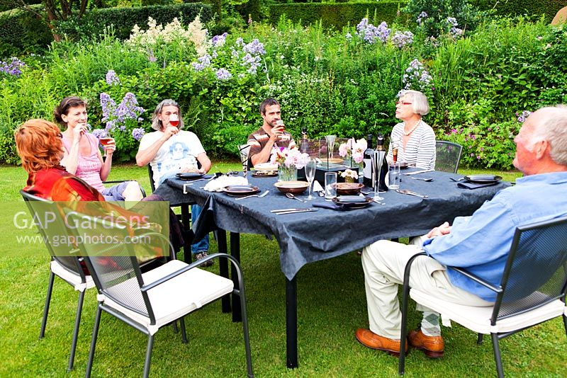 Socialising with friends around table on the lawn by the Crescent Border - Veddw House Garden, Monmouthshire, Wales