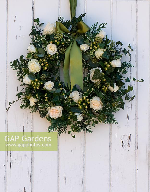 Christmas wreath hanging on white painted wooden door. Includes Rosa 'Artemis', Hypericum 'White Condor', Ivy and variegated Euonymus.