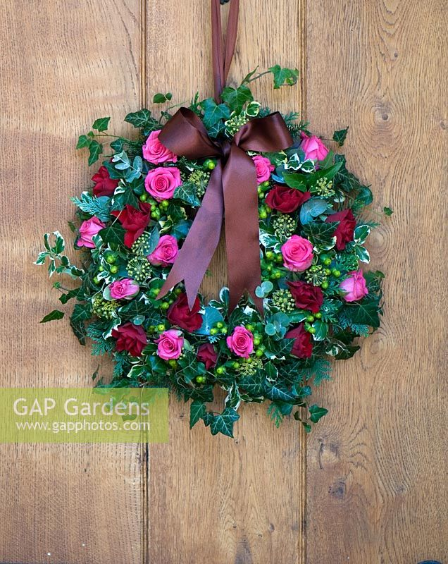 Christmas wreath hanging on oak front door, including Rose 'Tenga Venga', Rose 'Prestige', Hypericum 'Selva Romance', Ivy and Euonymus.