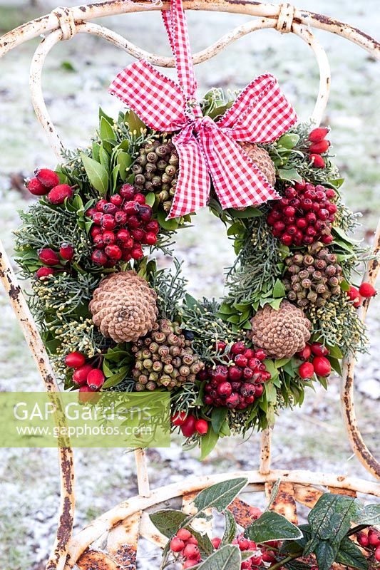 Frosted wreath with berries and cones tied with ribbon to old metal chair