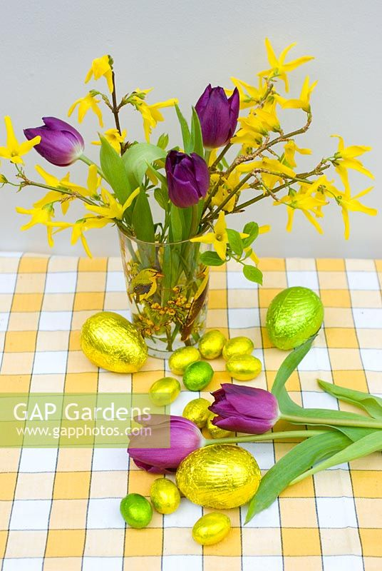 Flower arrangement of forsythia and purple tulips with foil wrapped easter eggs
