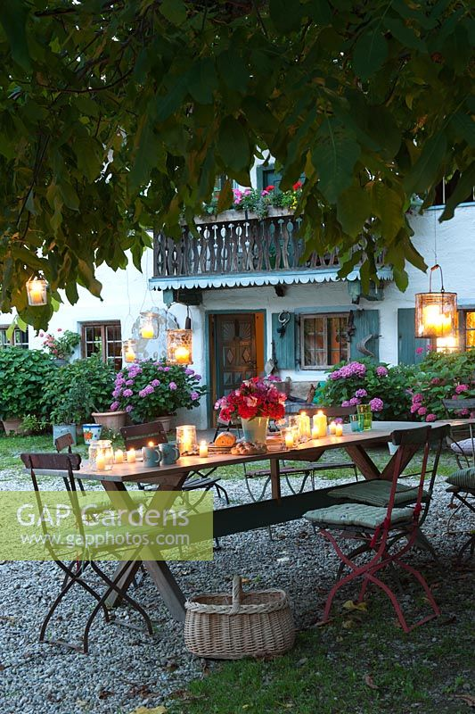 Long wooden table and seats in a country garden, decorated with candles and lanterns