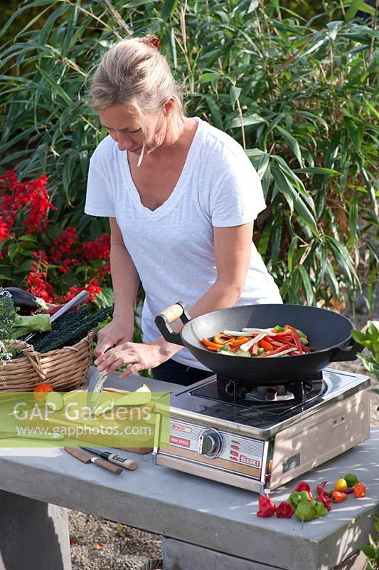Woman cooking vegetables outdoors