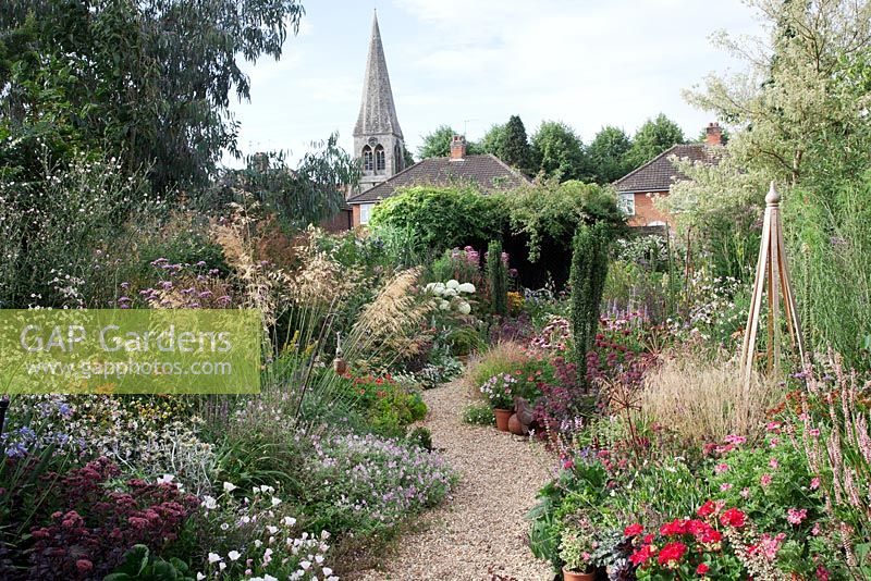 GAP Gardens - Overview of the garden with church view, a gravel path ...