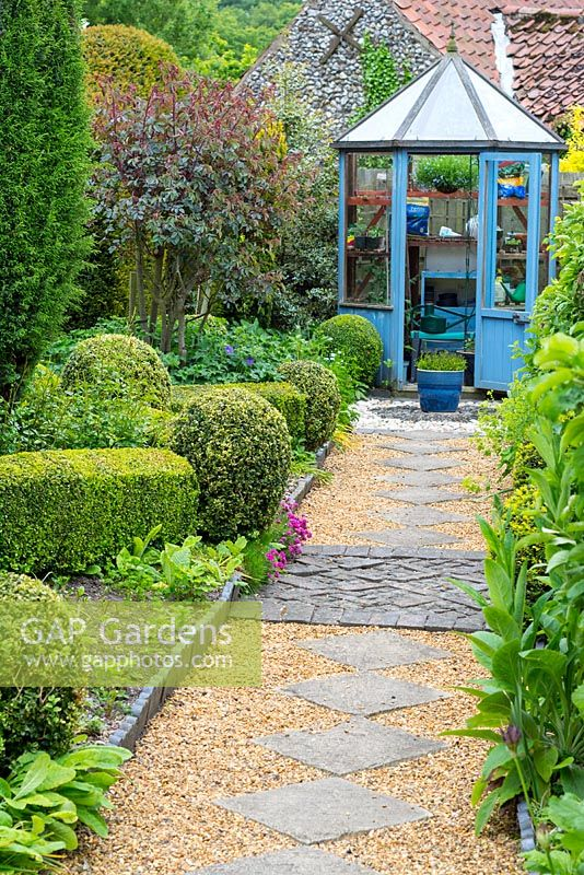 Cottage garden with slab and shingle path leading to hexagonal greenhouse