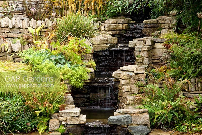 Waterfall with planting of Alchemilla mollis, Polygonatum, Dryopteris affinis Cristata, Blechnum penna and Carex 'Variegata'