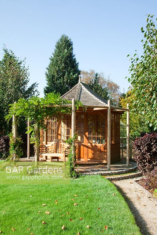 Autumnal garden with wooden Summer house. Planting of Fagus sylvatica 'Dawyck Gold', Betula utilis jacquemontii 'Doorenbos', Trachelospermum jasminoides and Wisteria sinensis 'Prolific'