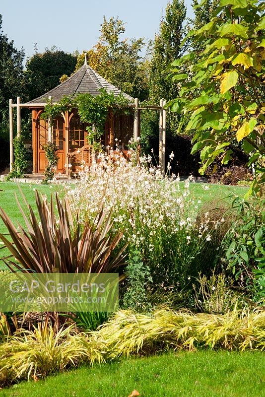 Small garden with summer house and planting of  Phormium tenax 'Sundowner', Hakonachloa macra alboaurea, white gaura, Trachelospermum jasminoides and Wisteria sinensis 'Prolific'