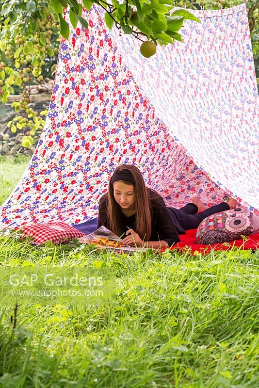 Young girl reading a book inside a tent