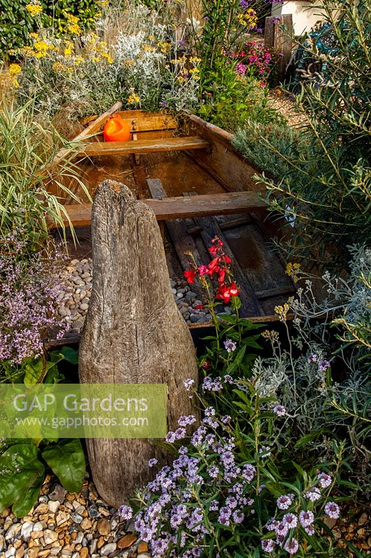 A Rowing Boat And Some Driftwood In The Coastal Themed Beach Garden, Driftwood  Gardens