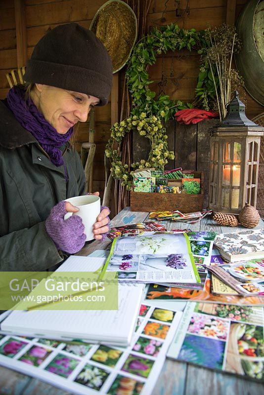 Woman sat in shed garden planning during Winter, for the following year to come.