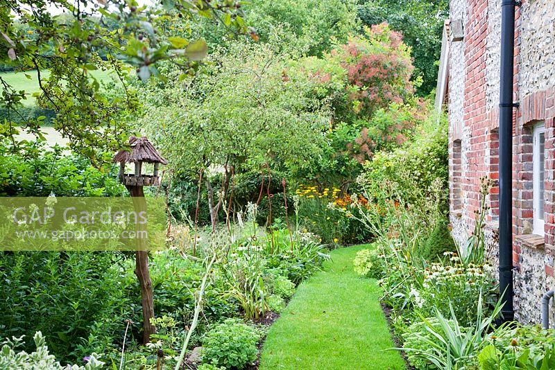 Rustic bird table and decorative metal plant stakes in late summer border