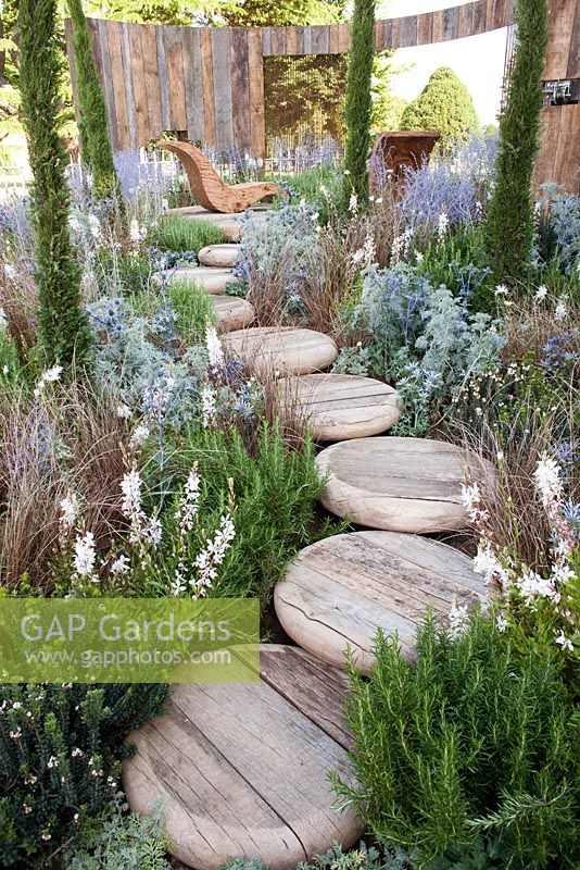 A room with a view.  RHS Hampton Court 2013. Stepping stone wooden path leading to patio with wooden chair. Eryngium x zabelii 'Big Blue', Rosmarinus officinalis, Carex buchananii, Anthemis punctata, Eryngium bourgatii, Gaura lindheimeri, Perowskia 'Blue Spire' and Cupressus sempervirens.