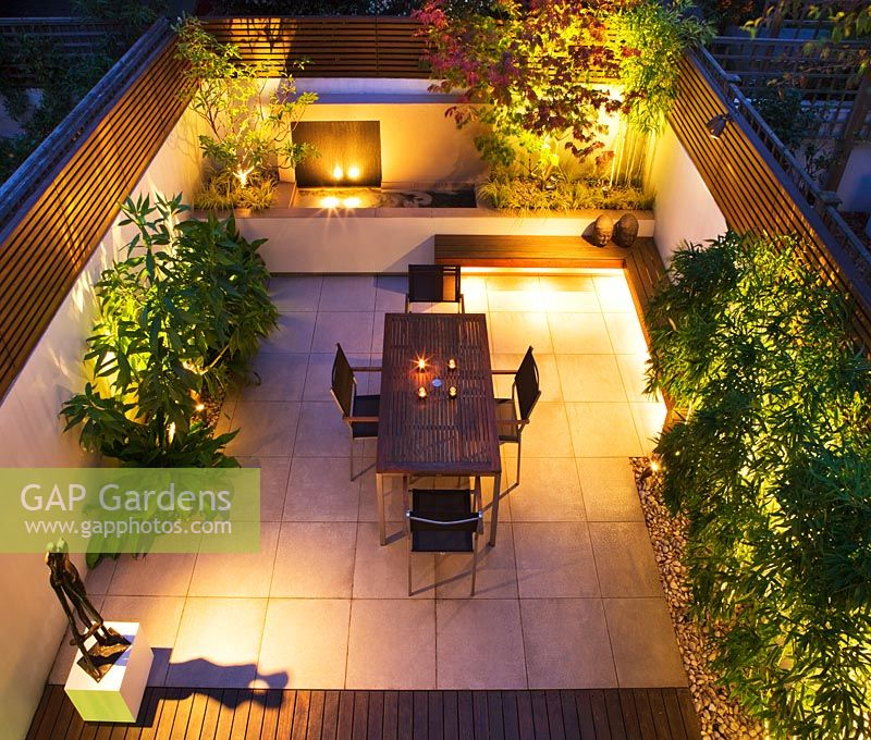Overview of modern minimalist garden lit up at night