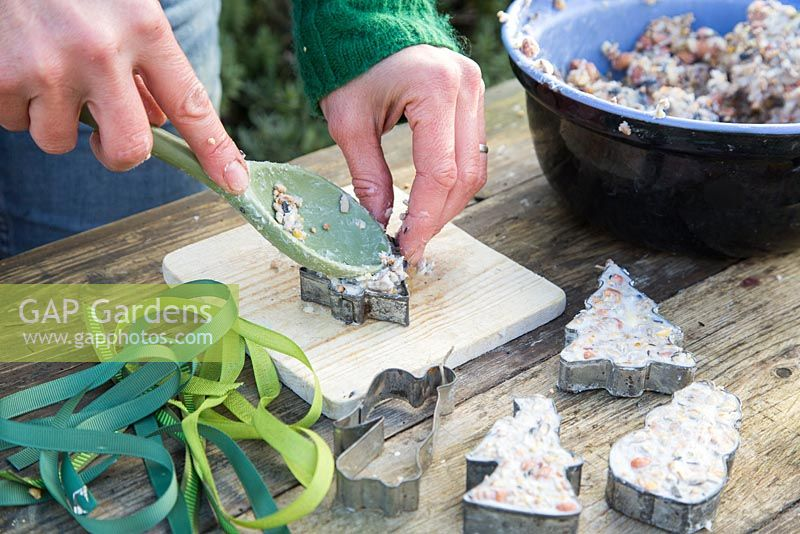 Filling cutters with mixture - making cookie cutter and pine cone bird feeders