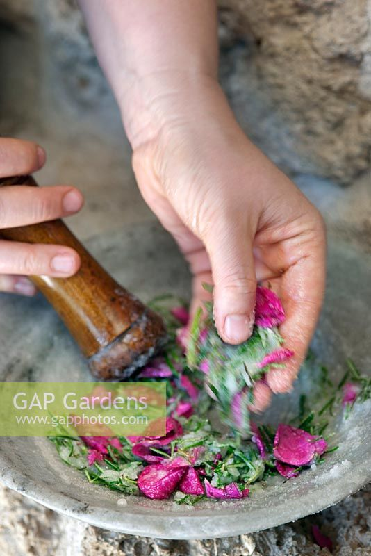 Using a pestle and mortar to create a spa treatment of rose petals, rosemary and salt