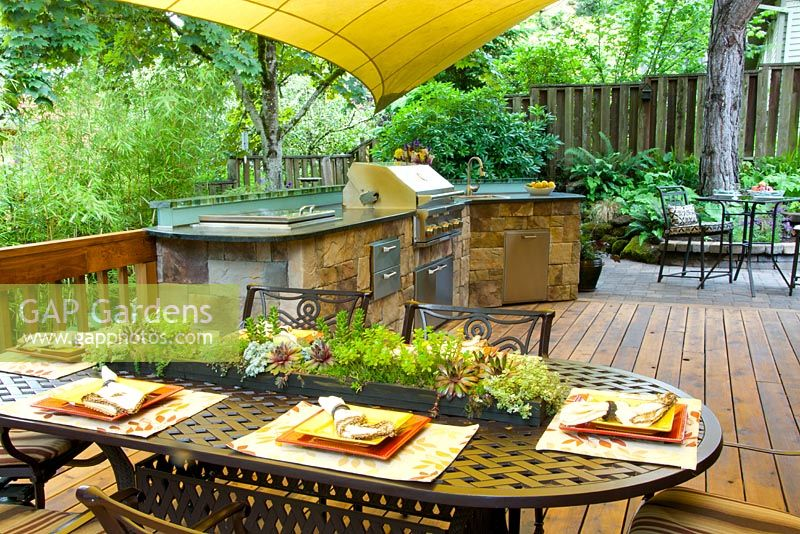 Summer outdoor kitchen with grill and sink on wooden deck. Wrought-iron chairs and table with succulent garland centerpiece.