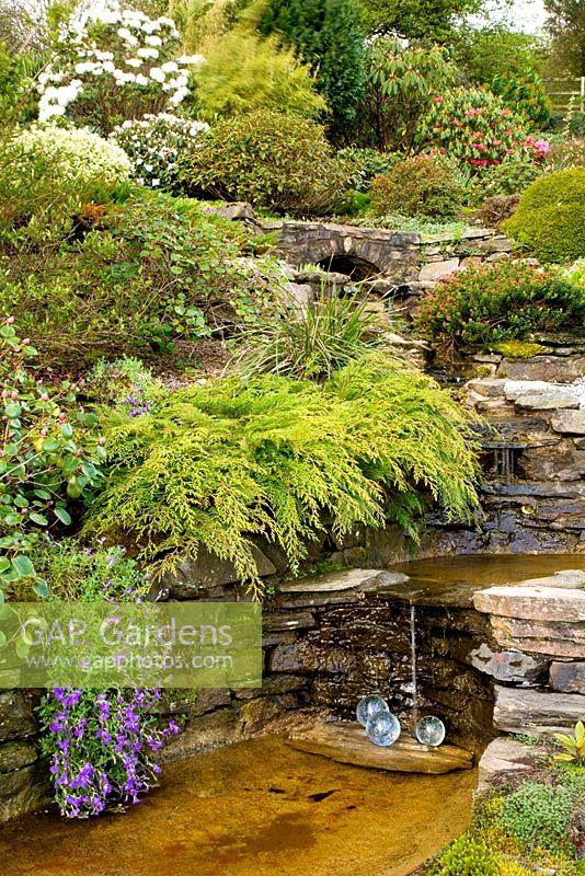 Waterfall Built Through Rock Garden With Juniper, Rhododendrons, Lobelia  And Glass Sculpture