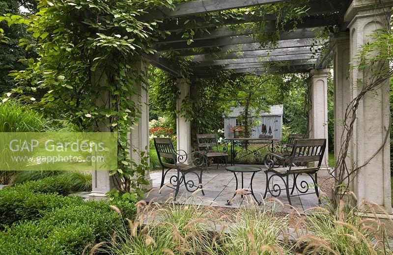 gap gardens garden chairs and table underneath a wood and concrete pergola covered with a kiwi. Black Bedroom Furniture Sets. Home Design Ideas