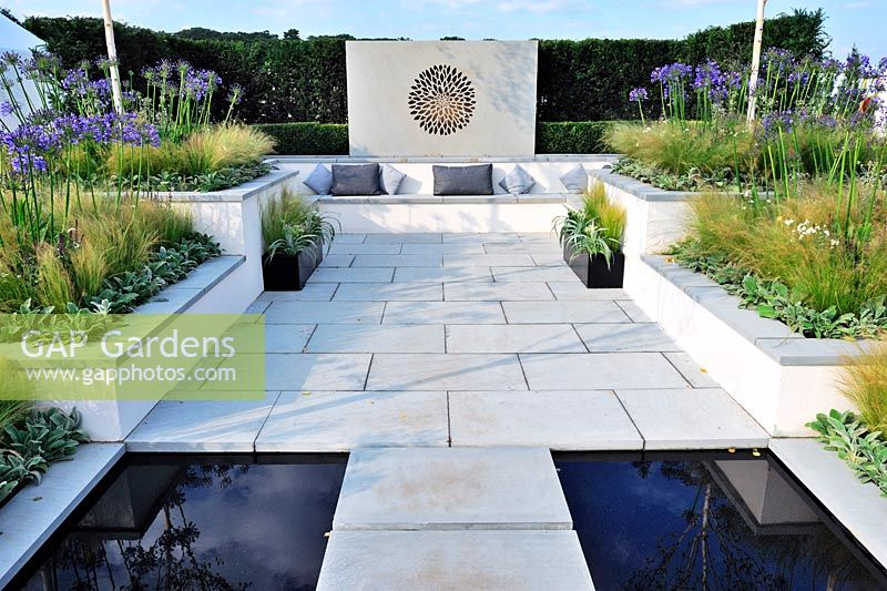 A low maintenance contemporary garden.Raised beds planted with grasses and agapanthus. Built in concrete seating. Description: Vogue. Designer: Belinda Belt Sponsor: London Stone Crowder's Nursery