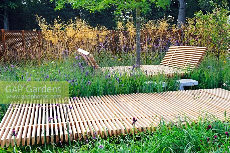 Extensive planting along Timber walkway and timber resting area. Grasses along metal fence. Description: The Sky is The Limit. Design: Sam Ovens