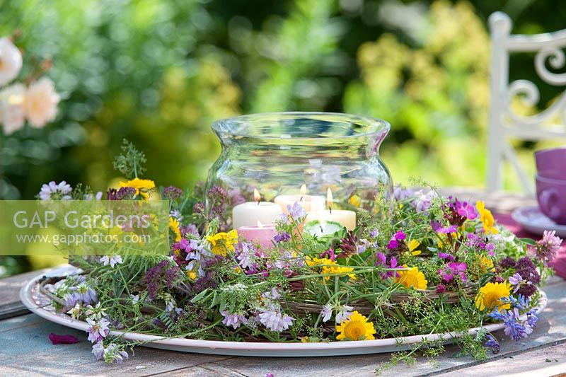 Wreath around glass lantern of candels made  from Galega, Anthemis, Origanum, Dianthus, Trifolium pratense  and Galium