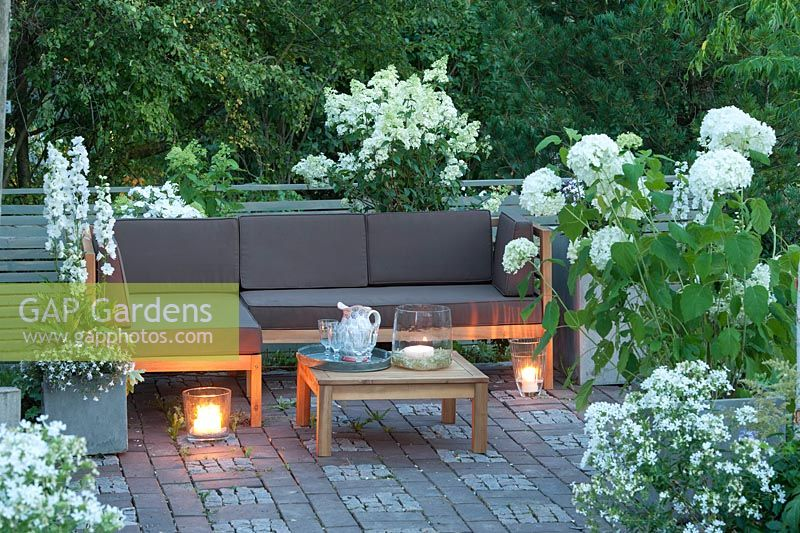 Terrace with furniture and plants including Hydrangea 'Annabelle' 'Limelight', Phlox, Delphinium 'Magic Fountain'