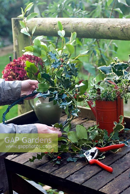 Christmas decorations from your garden - making wreath from picked branches of evergreens and flower heads