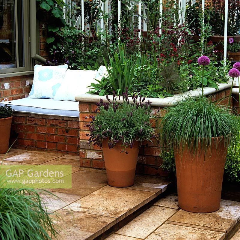 Raised flower bed doubles as side to brick seat with cushions, built in sunny position by conservatory.