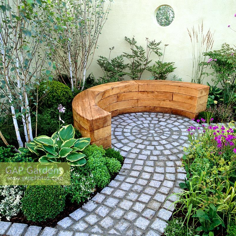 Pale lemon walls enclose tranquil courtyard, giving light airy feel. Granite sett path leads to circular courtyard. Curving wooden bench. Birch, hosta, box balls.