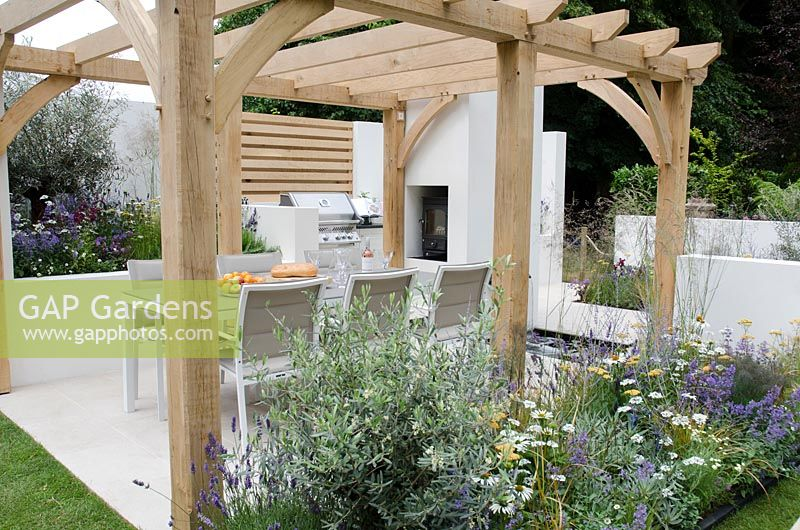 Seating area under pergola with BBQ and outdoor woodburner, Olearia x haastii in a border with Echinacea 'White Swan', Achillea 'Walther Funcke', Carex testacea, Nepeta 'Walkers Low' and Orlaya grandiflora, Al Fresco, RHS Hampton Court Palace Flower Show 2014