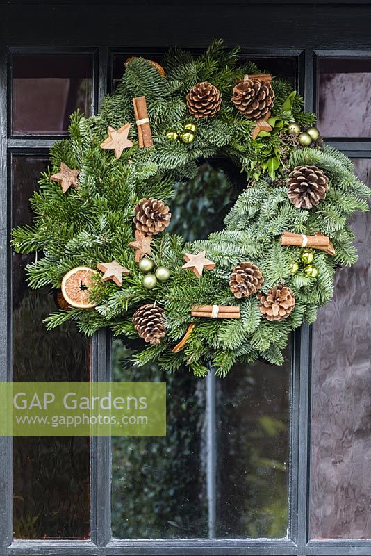 Christmas wreath decorated with fir cones, baubles, cinnamon sticks and wooden stars made by Sue Wright. Veddw House Garden, Devauden, Monmouthshire, Wales.UK.