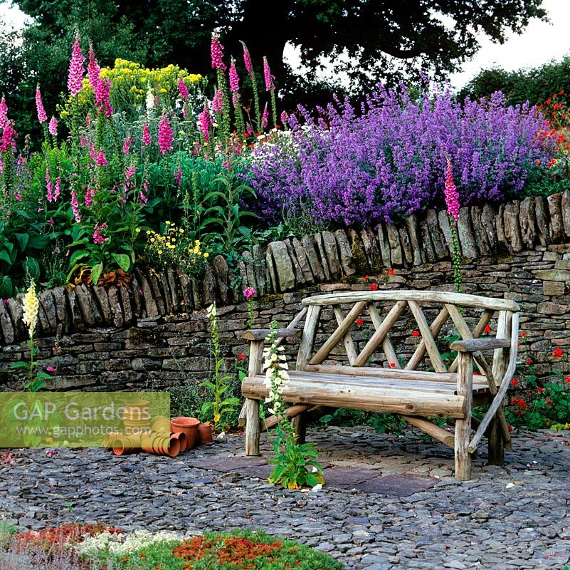 Sunken stone garden with wooden bench, white foxglove and red Geum 'Mrs Bradshaw' self-seeded in slate. On wall, Nepeta 'Six Hills Giant' and foxgloves.