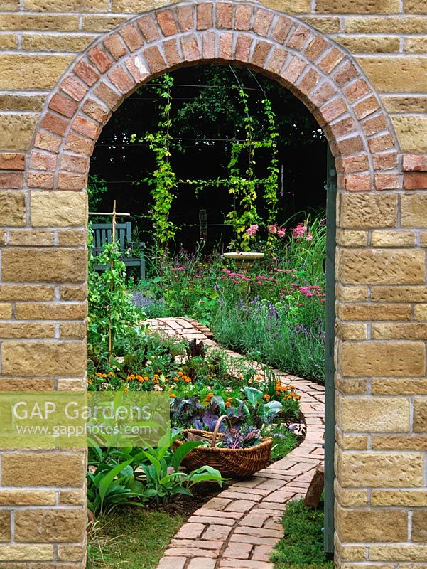 Framed by doorway in brick wall, view of brick garden path winding through vegetable beds to flowers - tagetes, achillea, lavender, sedum, astilbe and hop-clad gazebo.