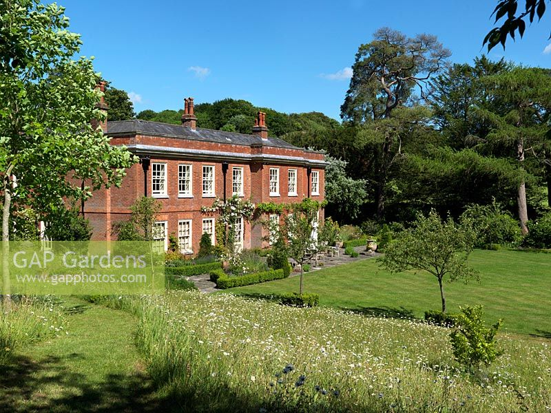 A Red Brick Country House With Patio And Large Lawn Bordered By Wildflower Meadow