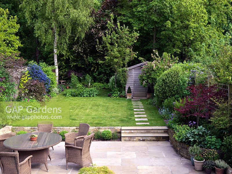 A family garden with stone patio with seating and dining area. Two steps lead up to the lawn. Seen from upstairs window. Wicker furniture