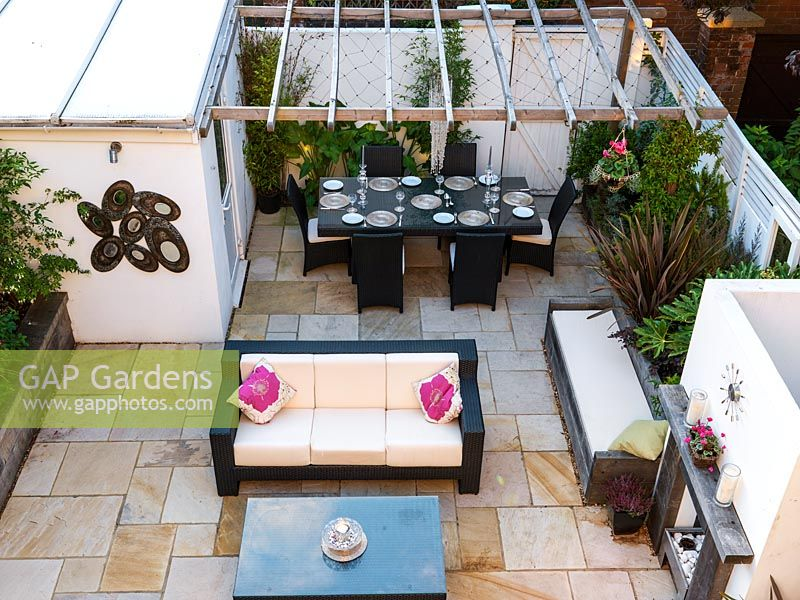 Outdoor room with sofas, dining table, gas effect fire, built-in seating, mirror, steel panel water feature, lighting, raised beds