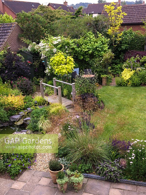 16 metre square back garden with gravel and boggy areas, wildlife pond, bridge, stream, trellis, lawn. Shady and sunny beds - shrubs, alpines, grasses, herbaceous plants.