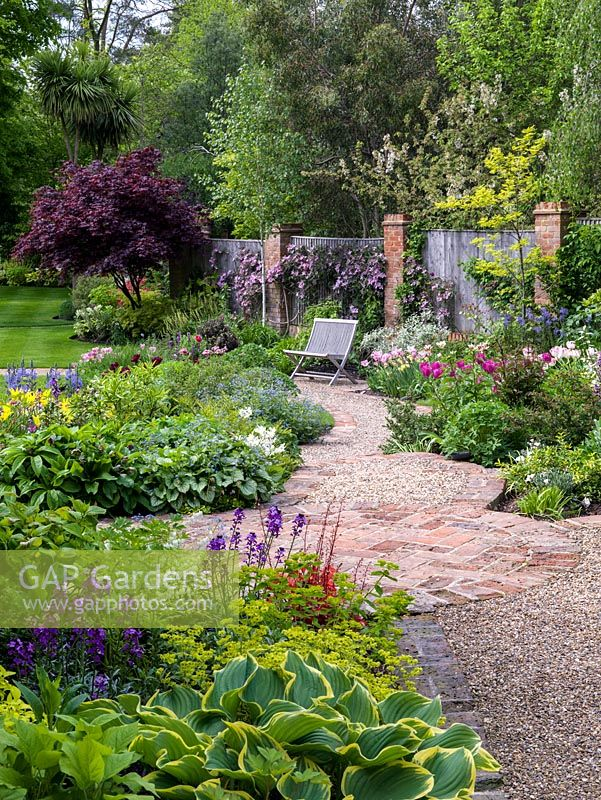Pathways meet at brick circle. Near bed - hosta, alchemilla, erysimum. Left bed - Brunnera Jack Frost, Tulipa West Point, camassia. Right bed - Tulipa Blue Ribbon, Rosalie. On fence - Clematis montana var. rubens.