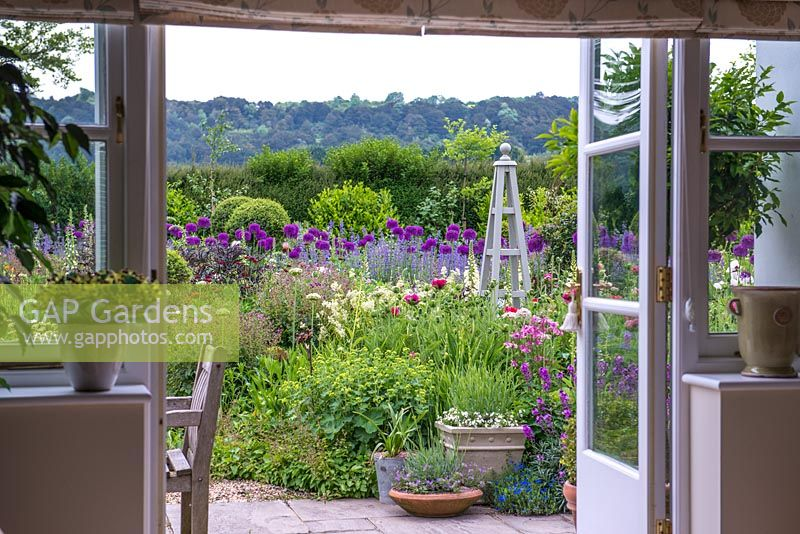 View Through french windows to a large early summer border.  This garden was planted only two years before these images were taken.