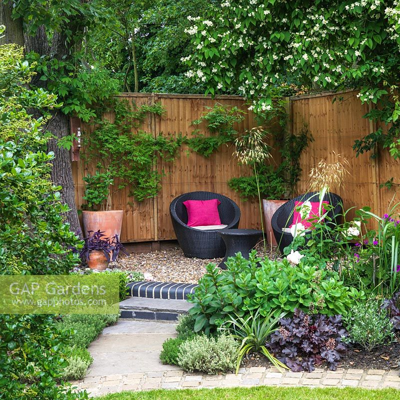 A sheltered seating area with contemporary garden furniture is raised in the corner of a modern garden.