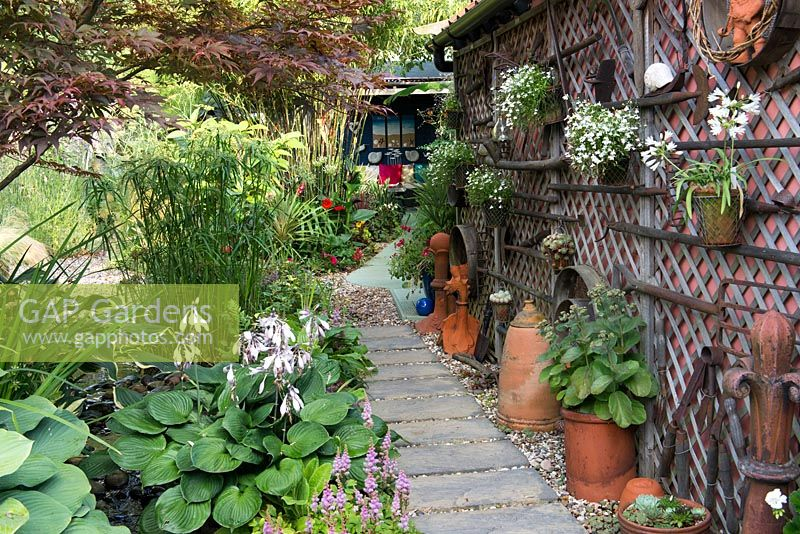 A town garden with narrow slab path besides a painted garage decorated with salvaged garden tools and hanging containers.