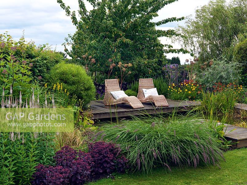 Wicker loungers on the pond side deck, behind a border including Veronicastrum virginicum 'Fascination',  Sedum telephium 'Purple Emperor' and Pennisetum alopecuroides,
