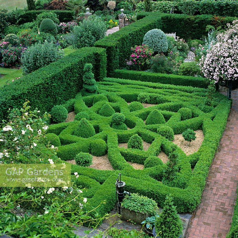 First floor view of knot garden created in clipped box hedges, balls and pyramids on gravel. Set against yew hedge and edged in reclaimed brick paths.