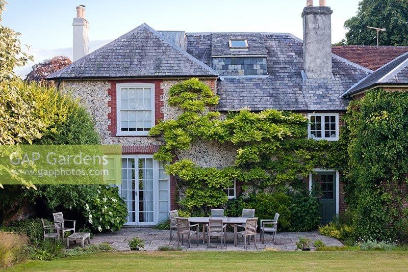 Patio with garden furniture at Hambledon House Hampshire. GAP Gardens   Patio with garden furniture at Hambledon House