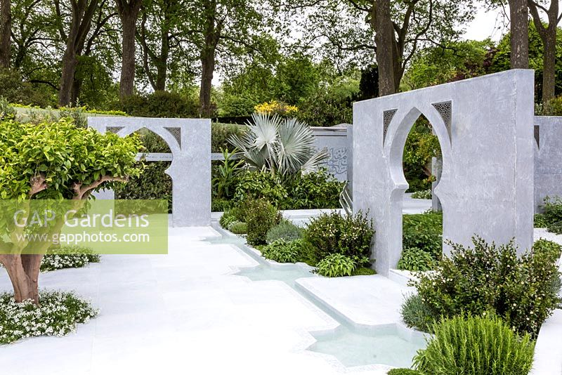 View of part of the garden with white marble paving, including Islamic archways and walls acting as dividers. Feature plants include Bismarckia nobilis at the back, Citrus aurantium in front, Myrtus sp., Rosmarinus officinalis, Salvia officinalis. Beauty of Islam. RHS Chelsea Flower Show, 2015